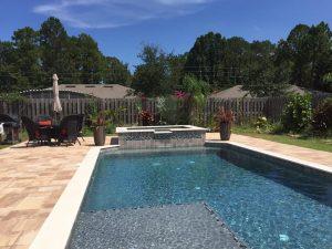 Custom pool design with sun shelf, raised spa, travertine coping, and large paver deck.